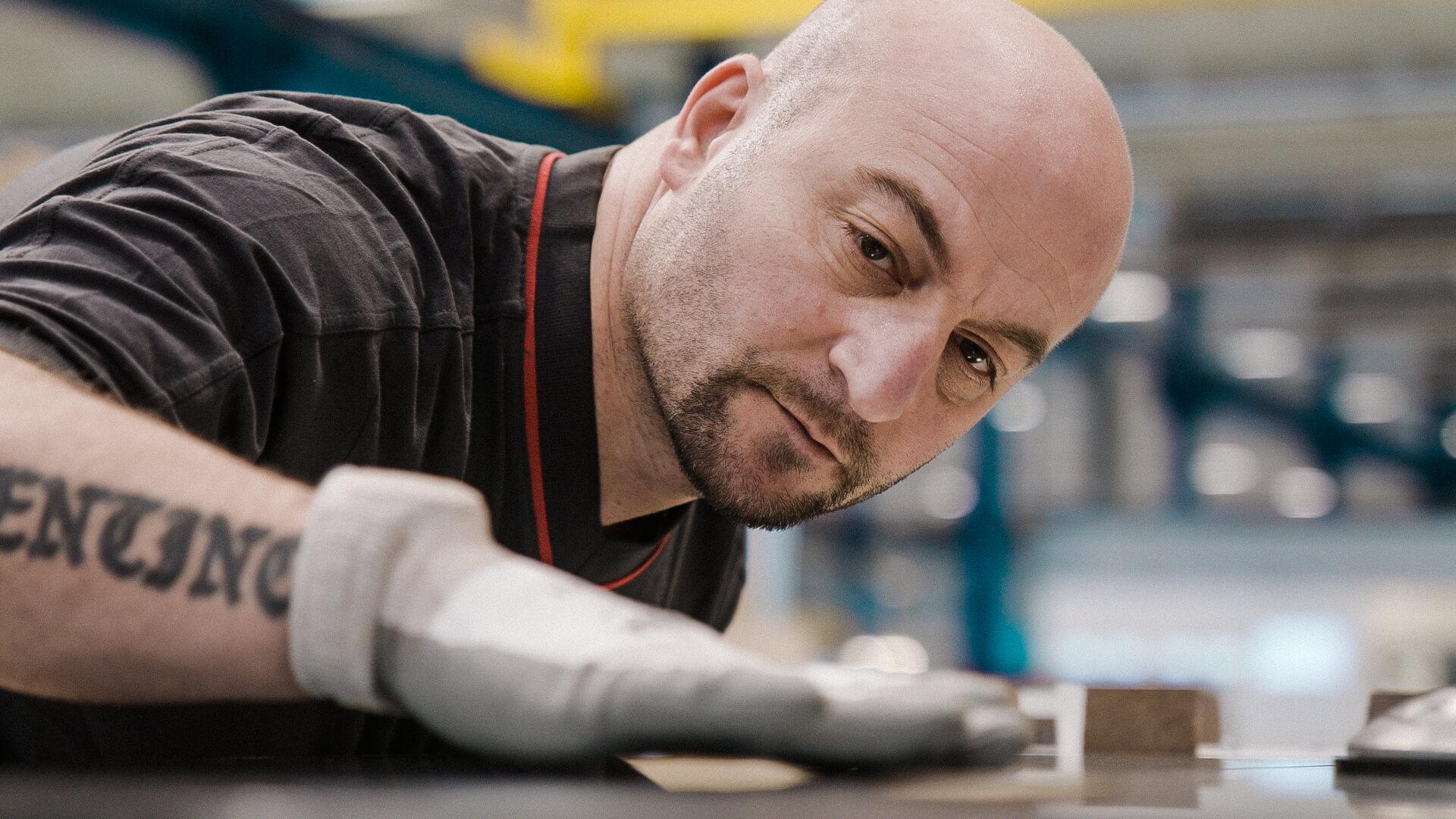 Imagefilm für Schindler Schweiz, Mitarbeiter befestigt letzte Teile in der Lift Manufaktur von Hand.